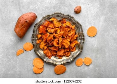 Baked potato, sweet chips with paprika, vegan snack or lunch on plate