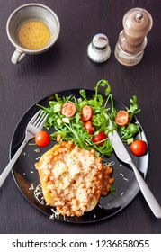 A baked potato topped with baked beans and cheese, served with a salad