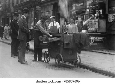 Baked potato vendor with a pushcart oven in New York's Lower East Side, c. 1915-20. The neighborhood was packed with Eastern European Jewish immigrants