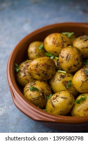 Baked potatoes with herbs in bowl