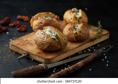 Baked potatoes with prosciutto and cheese in a pan