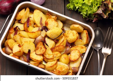 Baked potatoes in a roasting pan with garlic and onion on a wooden background