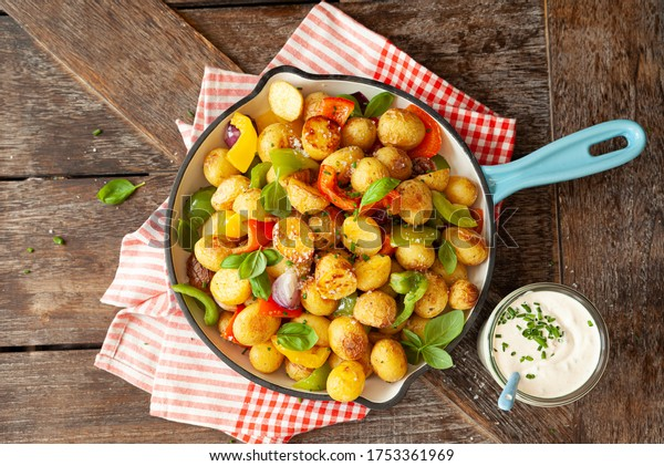 Baked pototoes with bell peppers in a cast iron skillet