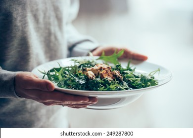 Baked pumpkin, blue cheese and arugula salad on white plate. Toned image