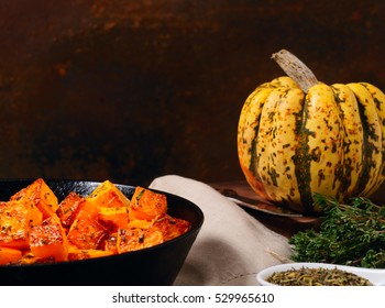 baked pumpkin cubes on old wooden background