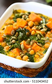 Baked pumpkin, kale and chickpea casserole with pumpkin seeds on top in casserole dish, photographed with natural light (Selective Focus, Focus one third into the image)