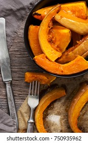 Baked pumpkin slices. Pumpkin in a bowl with tableware. Delicious dessert from vegetables