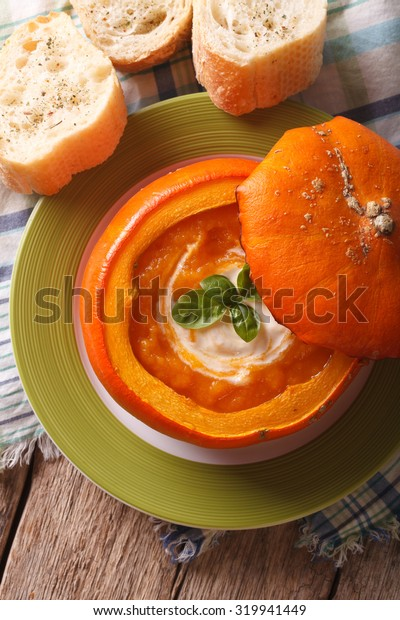 Baked pumpkin soup with sour cream and basil close-up. vertical top view
