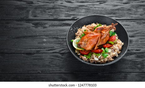 Baked quail with oatmeal and vegetables. On a black background. Top view. Free space for your text.