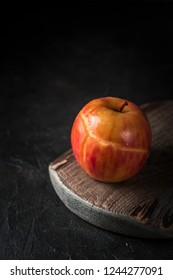 Baked red apple on wooden board on dark background.