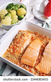 Baked red fish in tomato onion sauce in ceramic dish and fried potatoes with broccoli
