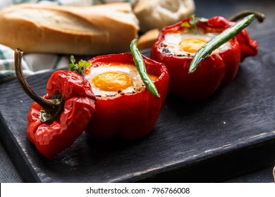 Baked red peppers stuffed with eggs and sausage with bread and green beans, close view