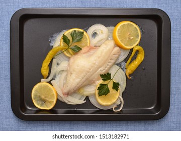Baked RedFish lemon and onions slices, fresh parsley, hot peppers in pan on blue table cloth