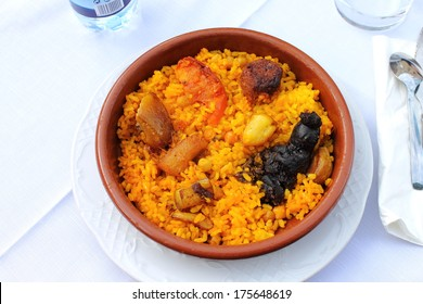 "Baked rice made in a pottery dish, accompanied by pork, chickpeas, blood sausage, tomato and garlic. Traditional ""arroz al horno"" from  the area of Xativa in Valencia, Spain"