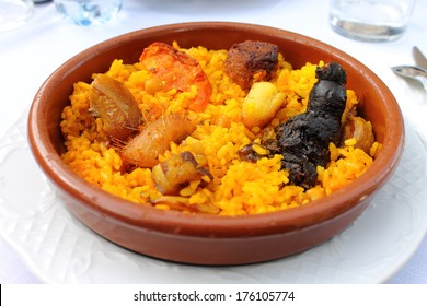 "Baked rice in a pottery dish accompanied by pork, chickpeas, blood sausage, tomato and garlic. Traditional ""arroz al horno"" from the area of Xativa in Valencia, Spain"