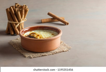 Baked rice pudding turkish dessert sutlac in earthenware casserole with cinnamon sticks