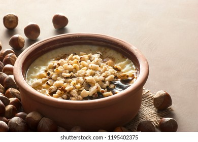 Baked rice pudding turkish milky dessert sutlac in earthenware casserole with hazelnuts