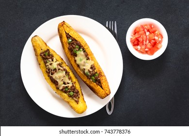 Baked ripe plantain stuffed with mincemeat, olive, green bell pepper and onion, traditional dish in Central America called Canoa de Platano (Plantain Canoe), served with tomato and onion salad