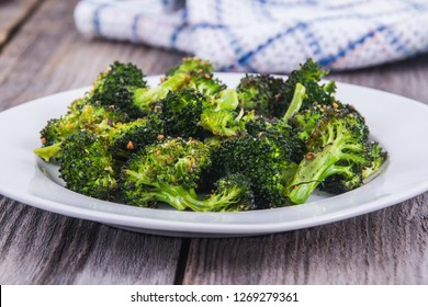 baked roasted garlic parmesan and olive oil broccoli side dish on wooden table