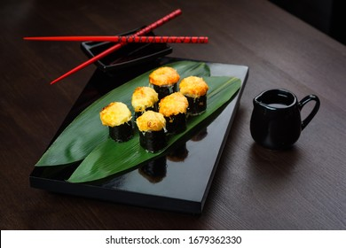 Baked rolls on the board with sauce and red chopsticks. Japanese cuisine