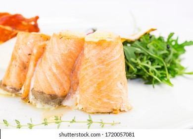 Baked rolls with salmon fillet then on a white plate in a restaurant.