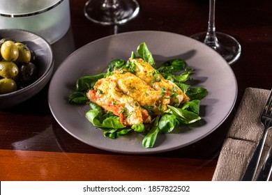 Baked salmon with cheese crust and fresh spinach on wooden table at restaurant side view