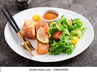 Baked salmon fillet with fresh vegetables salad. Healthy food. Ketogenic/paleo diet.