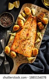 Filet de saumon cuit avec pommes de terre au raifort, citron et herbes fraîches servi sur une table en bois vue