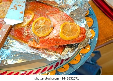 Baked salmon fillet with slices of lemon and spices, a potluck dish