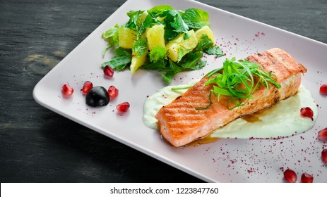 Baked salmon fillet with vegetables on a plate. On a wooden background. Top view. Free space for your text.