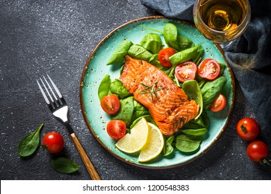 Baked salmon fish fillet with fresh salad from spinach and tomatoes on black stone table. Top view copy space.