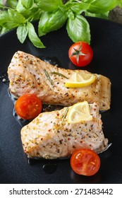 Baked salmon with herbs on the black plate