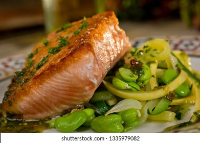 Baked Salmon on a bed of fava beans and capers drizzled with a chimichurri sauce