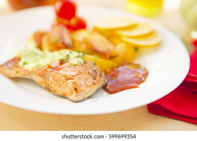 Baked salmon with potatoes and cream sauce on wooden table