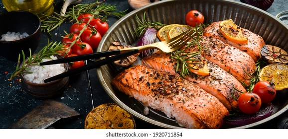 Baked Salmon with rosemary, lemon and vegetables. Recipe. Seafood. Side view Free space for text.