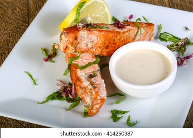 Baked salmon with sauce served lemon