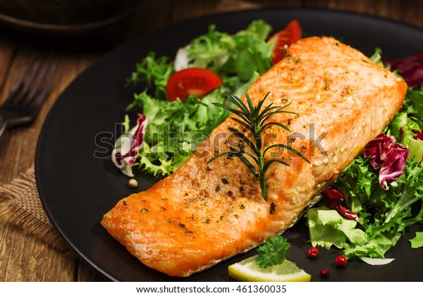 Baked salmon served with fresh vegetables.