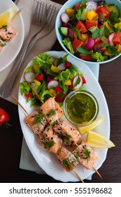 Baked Salmon skewers with white and black sesame served with fresh vegetable salad, lemon and herb sauce