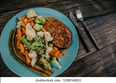 baked salmon steak with vegetables on a plate. wooden background