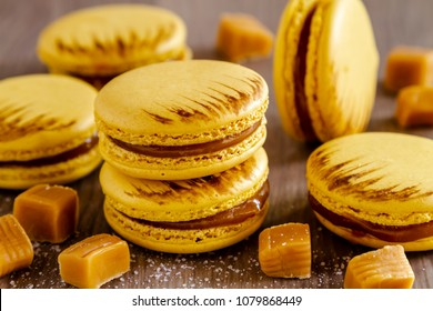 Baked salted caramel flavored french macarons sitting on wooden table surrounded by chucks of caramel and sea salt