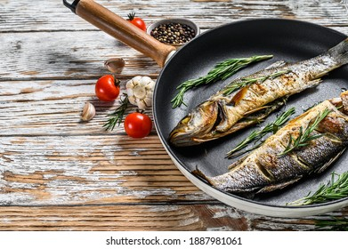 Baked sea Bass fish, grilled seabass. White wooden background. Top view. Copy space.