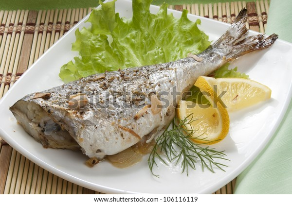 Baked sea bream with lettuce and lemon on the white plate