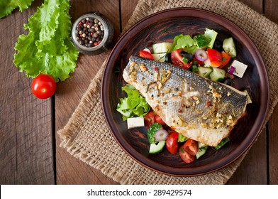 Baked seabass with Greek salad. Top view