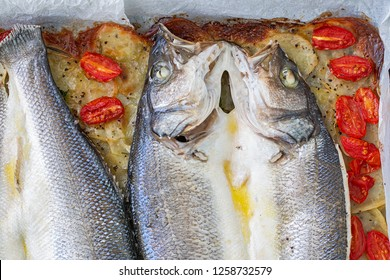 Baked seabass on layer of potatoes and some tomatoes.