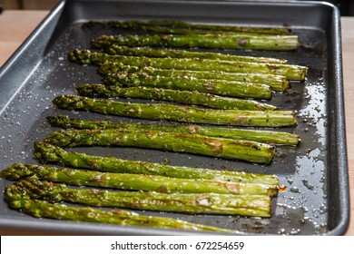 Baked seasoned asparagus on baking sheet with seasoning and olive oil