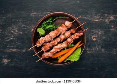 Baked Skewers of meat on a plate. On a wooden background. Top view. Copy space.