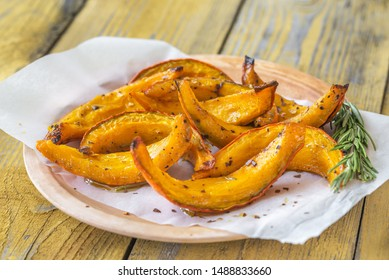 Baked slices of pumpkin with seasonings and rosemary
