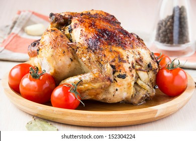 Baked small chicken with a ruddy crust, stuffed with apples on the wooden plate