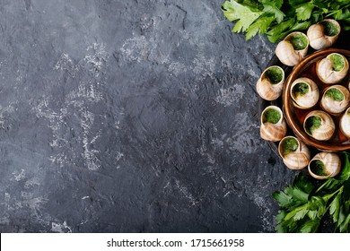 Baked snails with garlic butter and fresh herbs in a ceramic pan over dark texutre background. Top view, flat lay. Copy space