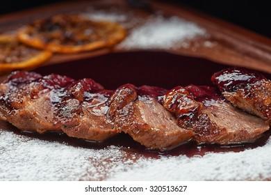 Baked spanish ham snack in sweat berry sauce on desk